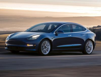 Tesla Model 3 (EU model) on a road with sun in the background