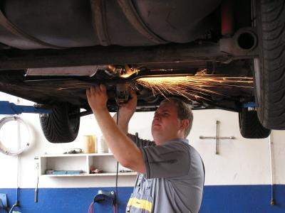 Someone carrying out repair maintenance on a car, from Helmut Gevert of FreeImages.com