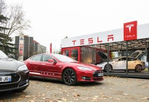 PARIS, FRANCE - NOVEMBER 29: Tesla Model S showroom and two luxury tesla cars outside and one inside. Tesla is an American company that designs, manufactures,