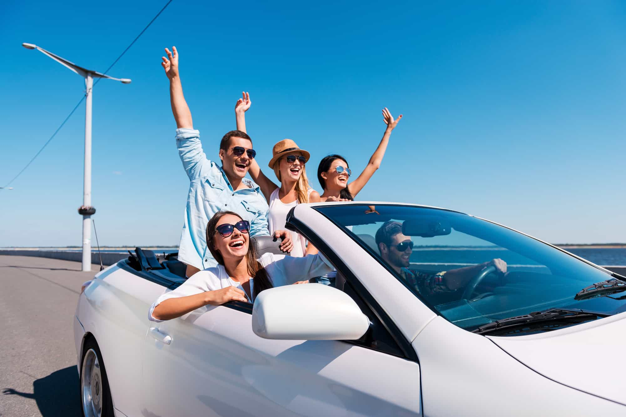Four people in a convertible car enjoying a road trip