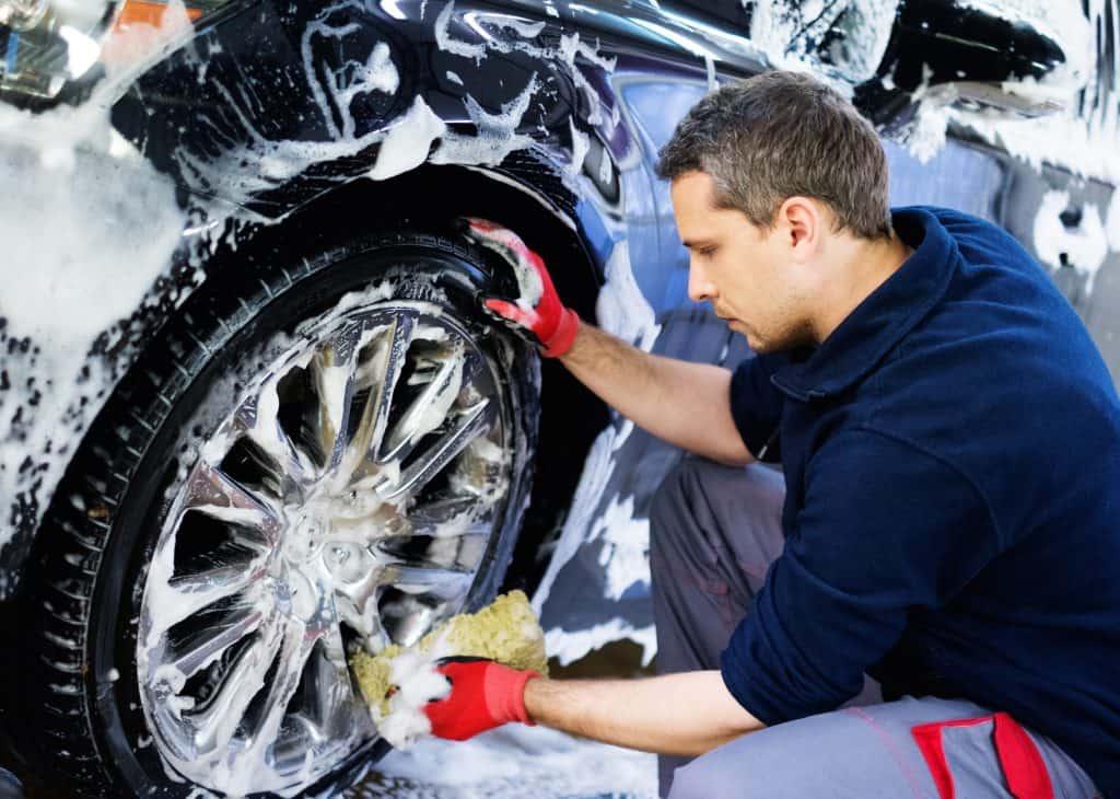 Someone hand washing a cars wheels
