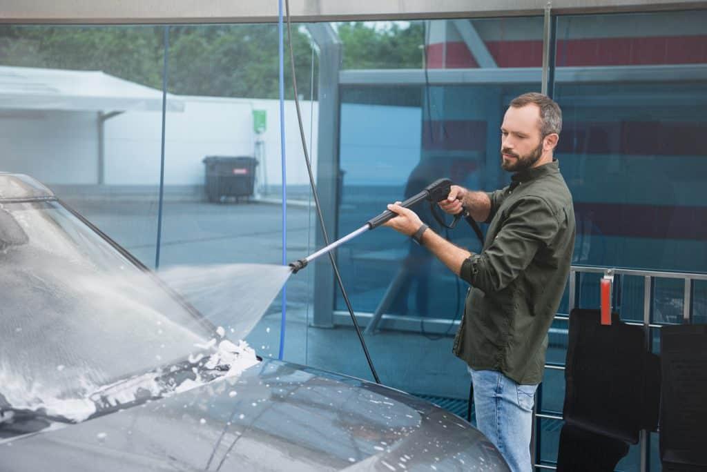 Someone jet washing a cars bonnet