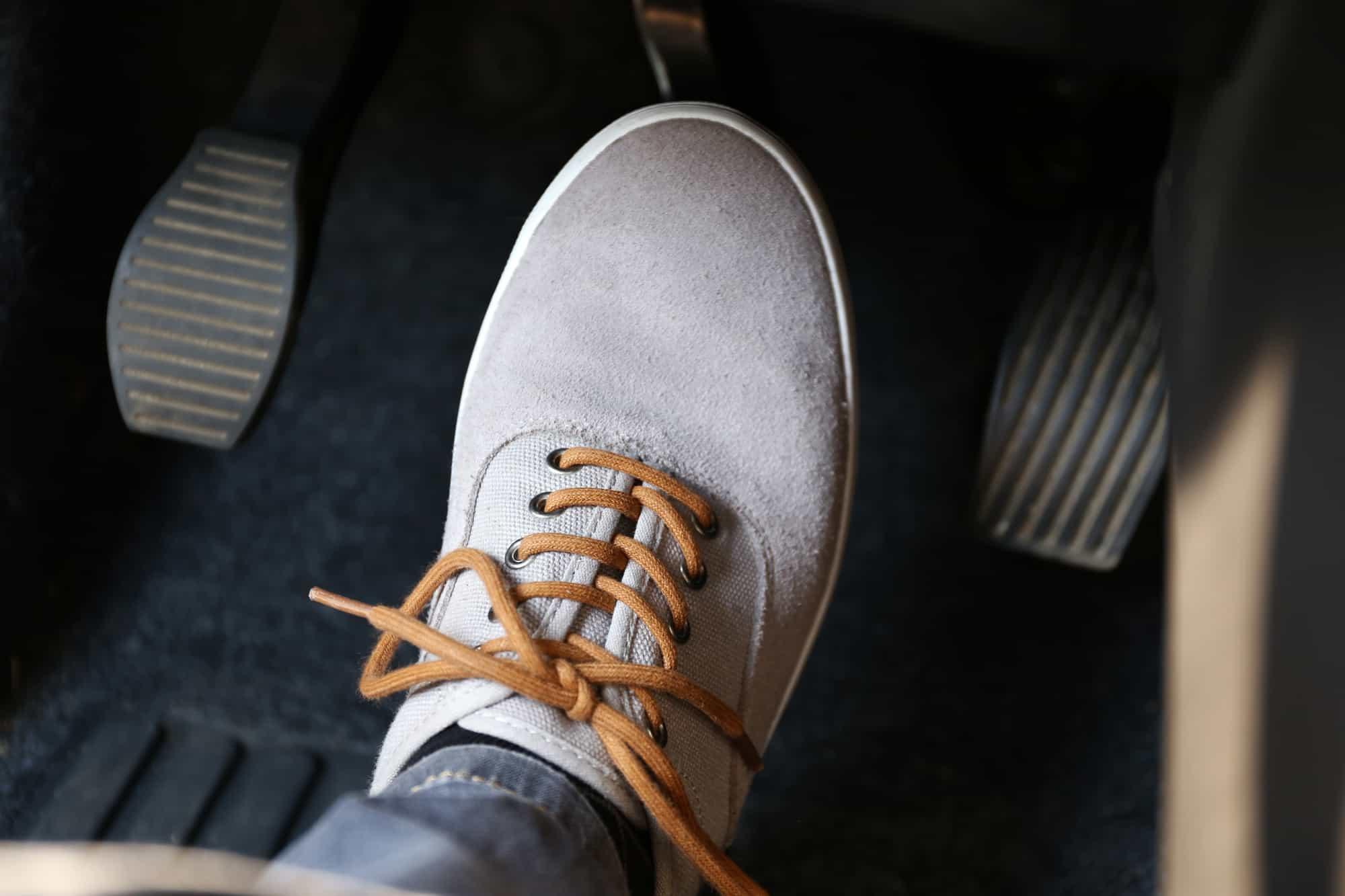 A Human foot pressing a car pedal