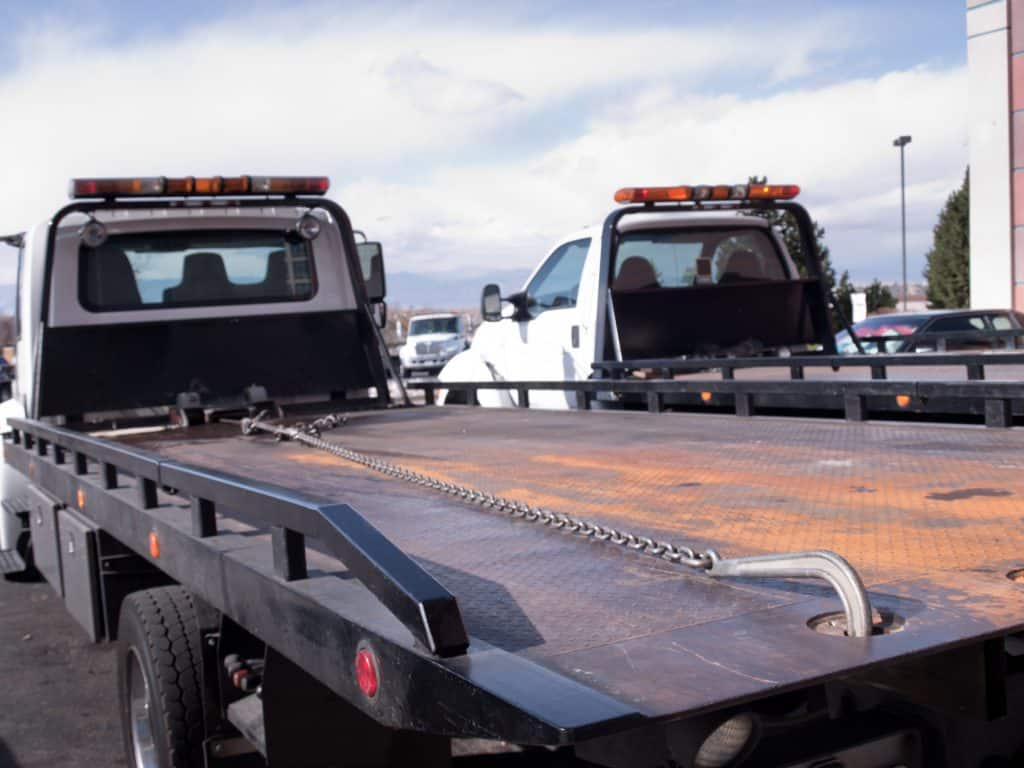 A flat bed tow truck