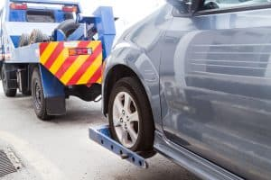 A tow truck towing a broken down car with a dolly to lift it off the ground