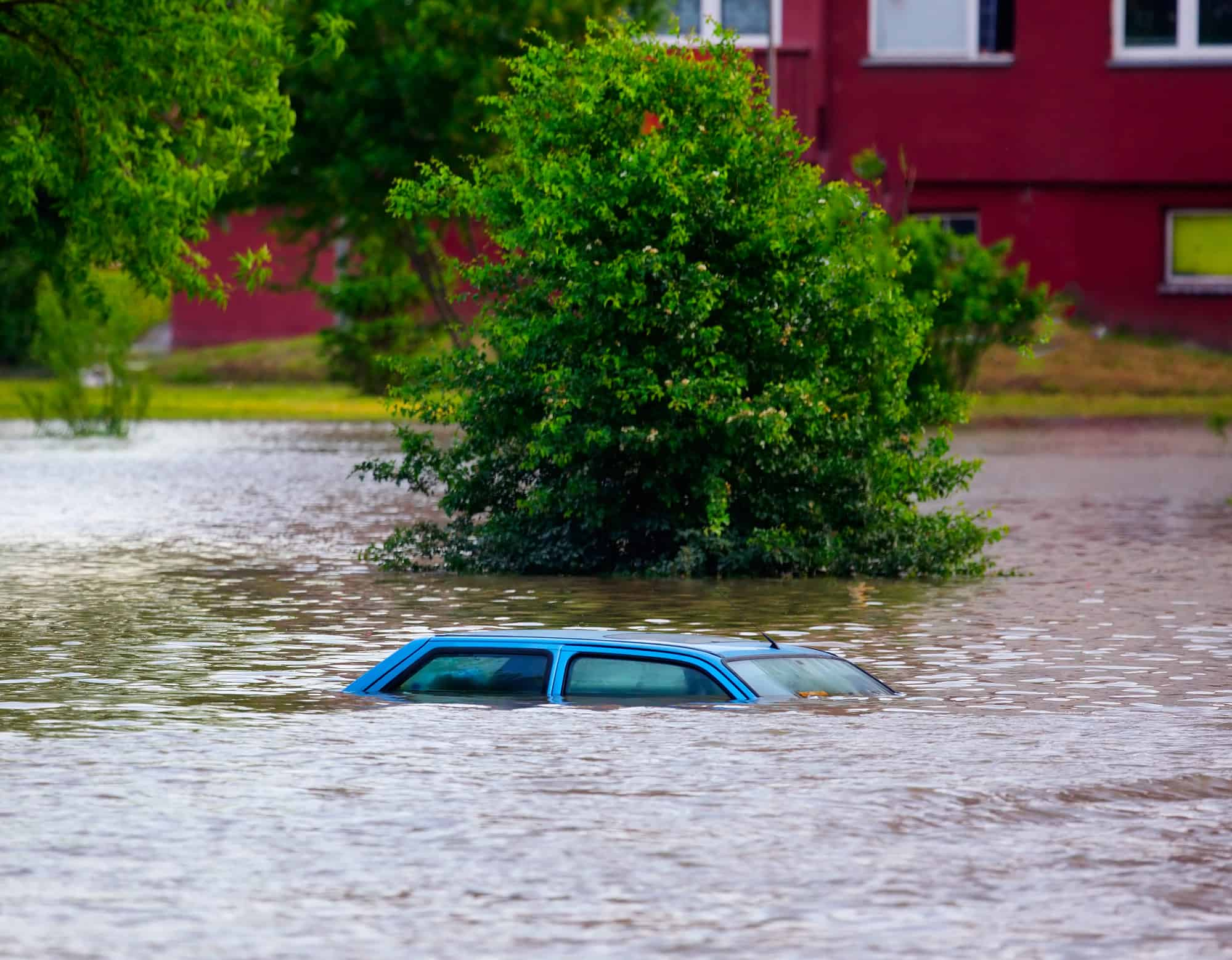 A very flooded area with only the top of a car visible