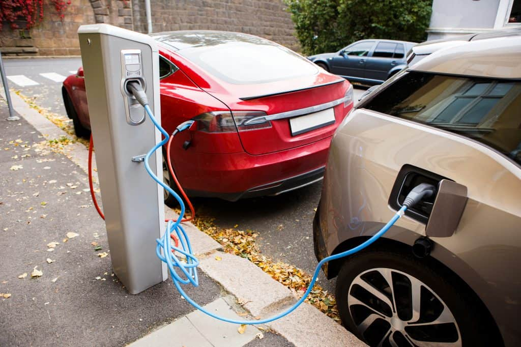 Two EVs charging on a public street